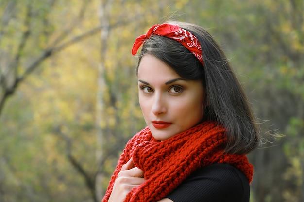 Belle jeune femme dans un manteau blanc au crochet écharpe rouge et chapeau noir portrait en plein air d'automne