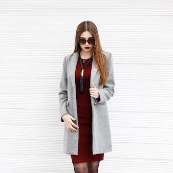Belle jeune femme dans un manteau gris et des lunettes de soleil près d'un mur en bois vintage
