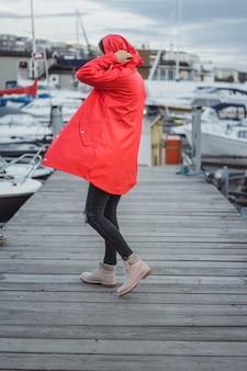 Belle jeune femme dans un manteau rouge dans le port de yacht. stockholm, suède