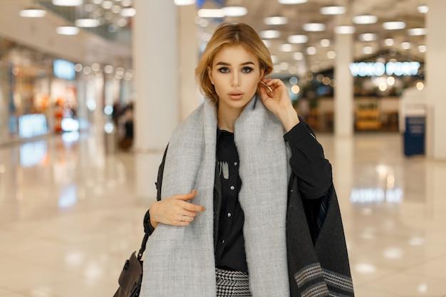Belle jeune femme dans un manteau tendance élégant au centre commercial
