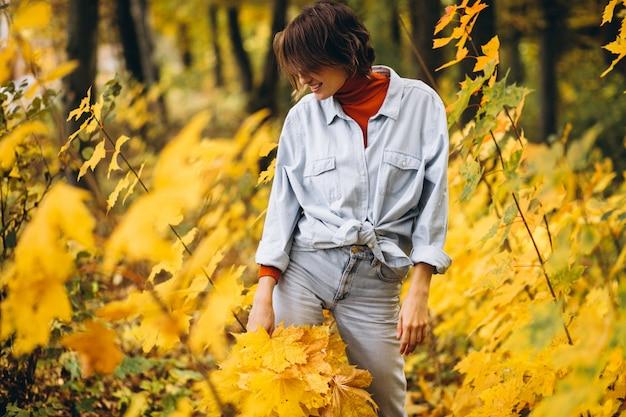 Belle jeune femme dans un parc d'automne rempli de feuilles