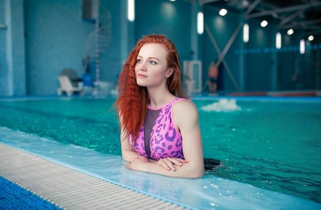 Belle jeune femme dans la piscine couverte.