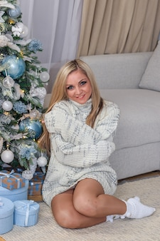 Belle jeune femme dans le pull assis sous le sapin de noël. blond