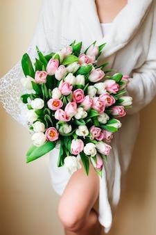 Belle jeune femme dans une robe de chambre blanche posant avec un bouquet de tulipes roses et blanches tendres.