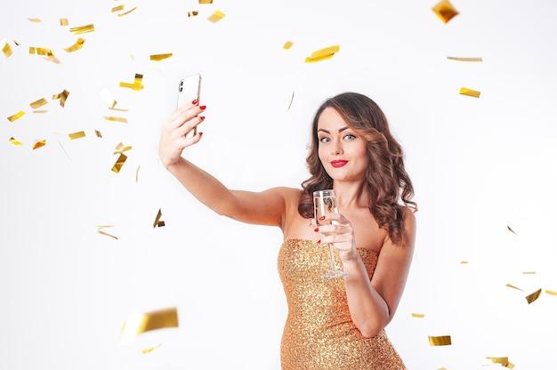 Belle jeune femme dans une robe dorée boit du champagne, fait un selfie sur un smartphone, s'amusant lors d'une fête avec des confettis dorés sur fond blanc