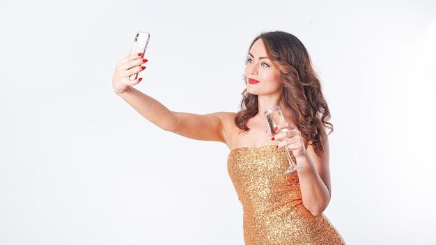 Belle jeune femme dans une robe dorée boit du champagne, fait un selfie sur un smartphone, s'amusant lors d'une fête sur fond blanc