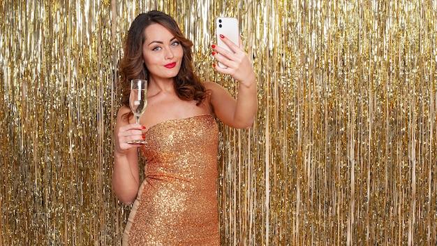 Belle jeune femme dans une robe dorée boit du champagne, fait un selfie sur un smartphone, s'amusant lors d'une fête sur un fond d'or brillant