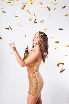 Belle jeune femme dans une robe dorée boit du champagne, s'amusant lors d'une fête avec des confettis dorés sur fond blanc