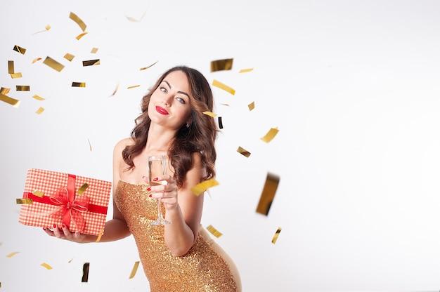 Belle jeune femme dans une robe dorée boit du champagne, tenant une boîte-cadeau rouge, s'amusant lors d'une fête avec des confettis dorés sur fond blanc