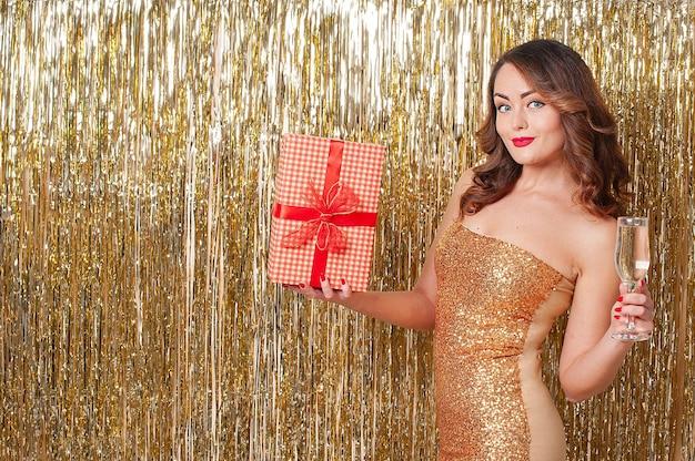 Belle jeune femme dans une robe dorée boit du champagne, tenant une boîte-cadeau rouge, s'amusant lors d'une fête sur un fond d'or brillant