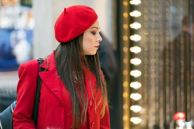 Belle jeune femme dans une robe rouge et un chapeau tenant des sacs à provisions et vérifiant un magasin en plein air dans un cadre de la ville moderne