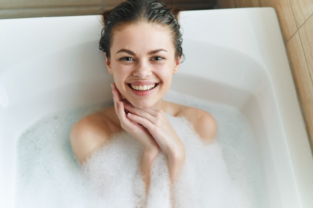 Belle jeune femme dans sa belle baignoire blanc comme neige repose et se détend, baignoire avec mousse