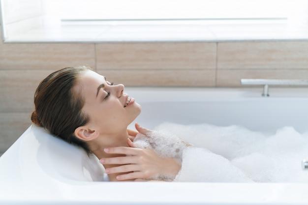 Belle jeune femme dans sa belle baignoire blanche comme la neige se repose et se détend, belle preuve, baignoire avec mousse