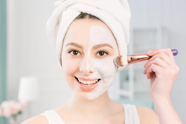 Une belle jeune femme dans une serviette de bain après une douche et un nettoyage de la peau applique un masque d'argile sur le visage avec une brosse cosmétique. beauté, santé, concept de cosmétologie. mode de vie. soin de la peau