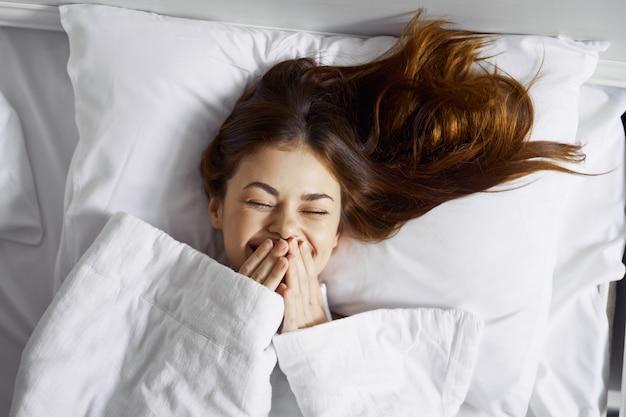 Belle jeune femme dans son beau lit blanc comme neige se détend et se détend, belle preuve