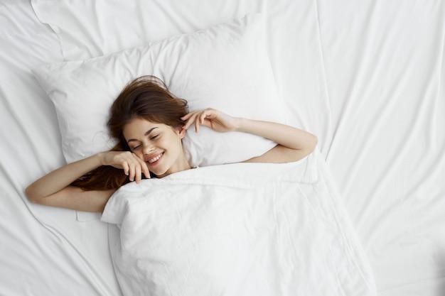 Belle jeune femme dans son beau lit blanc comme neige se détend et se détend,
