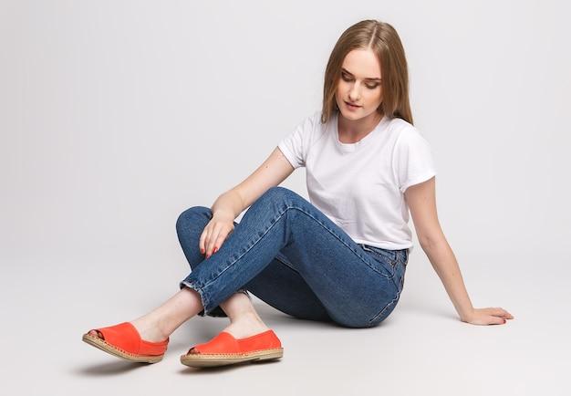 Belle jeune femme dans un t-shirt blanc et un jean sur un sol blanc
