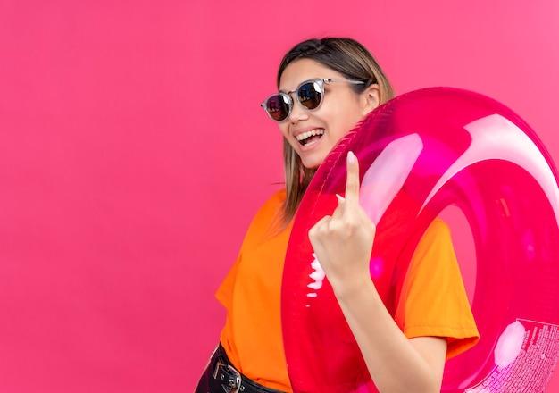 Une belle jeune femme dans un t-shirt orange portant des lunettes de soleil souriant et montrant l'index tout en tenant l'anneau gonflable rose sur un mur rose
