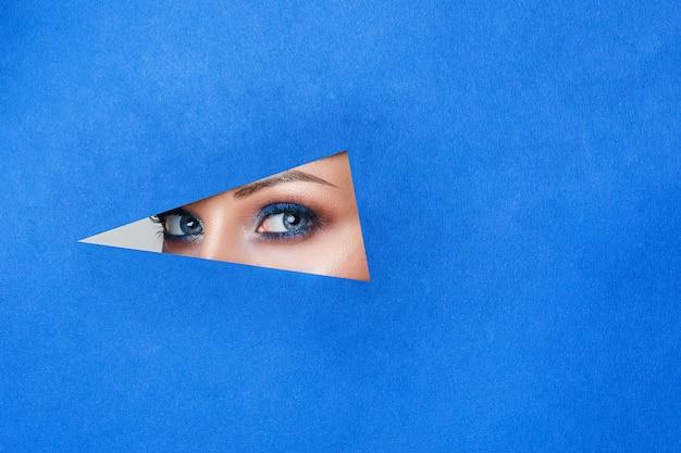 Belle jeune femme dans un trou de papier bleu, beau maquillage lumineux,