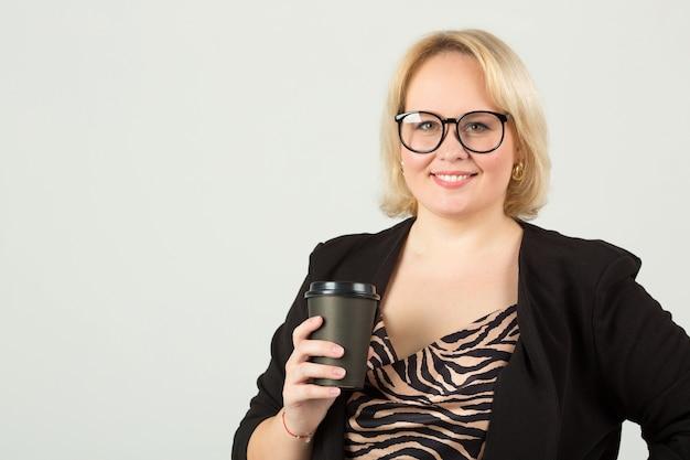 Belle jeune femme dans des verres avec une tasse de café