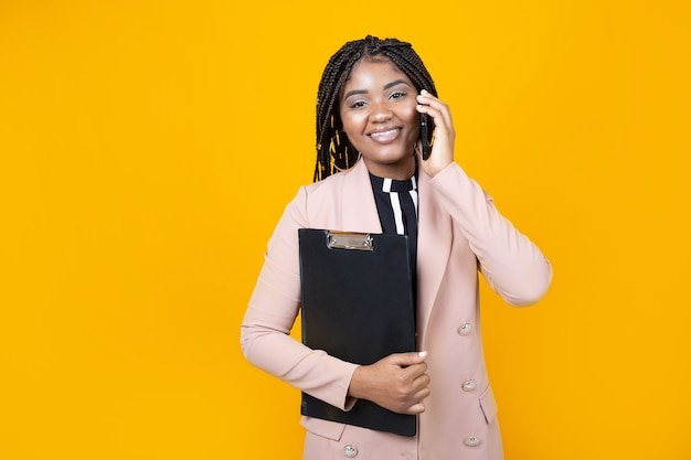 Belle jeune femme dans une veste avec un dossier sur un fond jaune avec un téléphone mobile