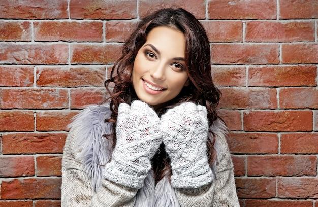 Belle jeune femme dans des vêtements chauds, debout près du mur de briques