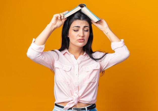 Belle jeune femme dans des vêtements décontractés tenant un livre sur la tête étant bouleversée debout sur orange