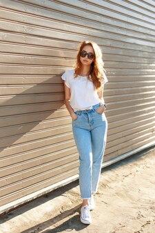 Belle jeune femme dans des vêtements vintage élégants pose près du mur