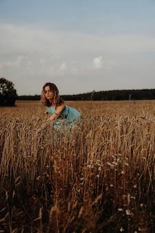 Belle jeune femme dansant sur le terrain au coucher du soleil