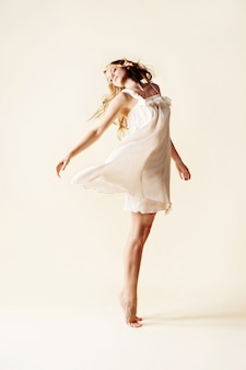 Belle jeune femme danse, fond clair studio.