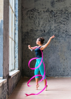 Belle jeune femme danse avec ruban rose