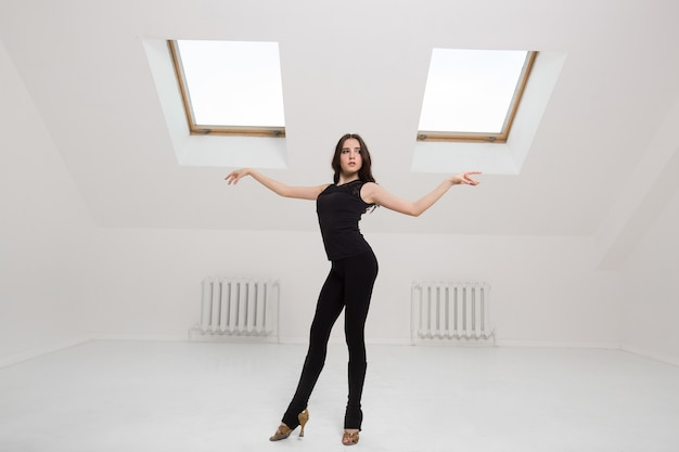 Belle jeune femme danse en studio