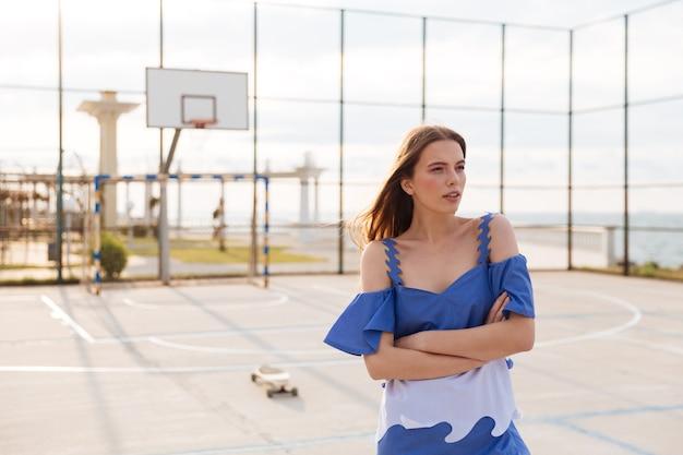 Belle jeune femme debout avec les bras croisés sur le basket-ball en plein air
