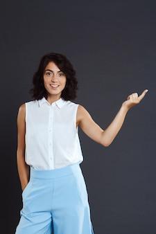 Belle jeune femme debout sur un mur gris et pointant son doigt
