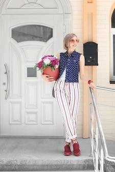 Belle jeune femme debout près de la porte avec des fleurs de pivoine dans une boîte-cadeau, à l'extérieur