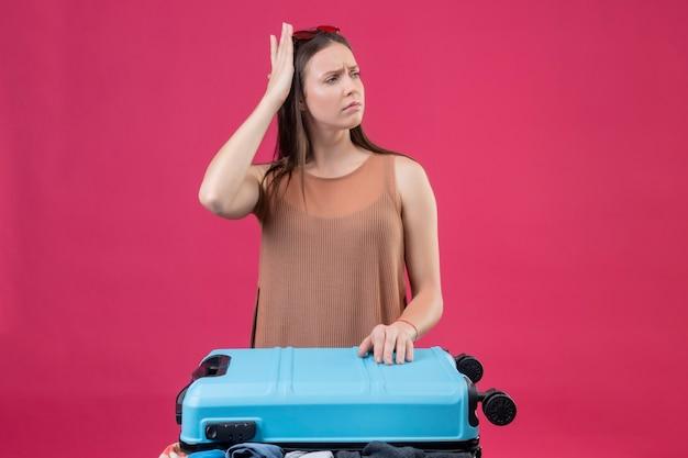 Belle jeune femme debout avec valise de voyage à côté de l'expression pensive de la moelle à la confusion sur fond rose