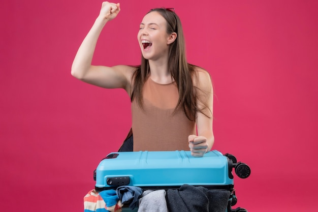 Belle jeune femme debout avec valise de voyage levant le poing après une victoire sortie et heureuse sur fond rose