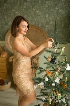 Une belle jeune femme décore un arbre de noël