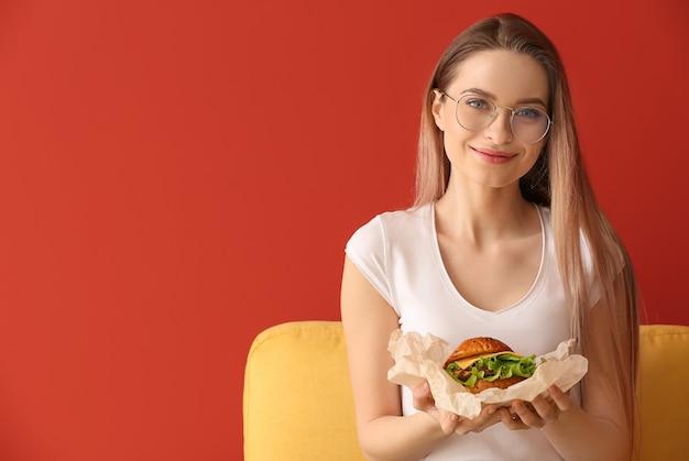 Belle jeune femme avec un délicieux burger sur la couleur