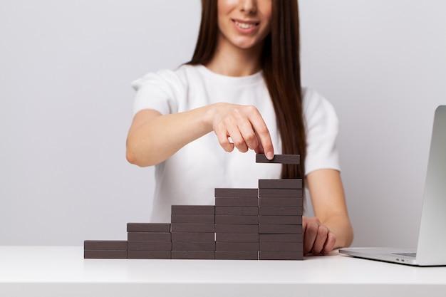 Belle jeune femme démontre sur le concept de développement des affaires de barres en bois