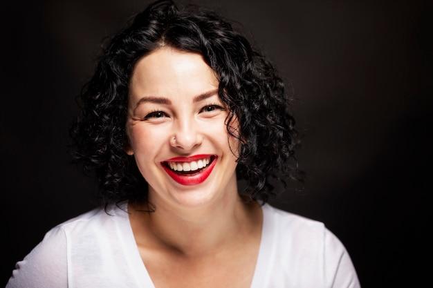 Belle jeune femme avec des dents blanches et lisses rit. brune lumineuse aux cheveux bouclés