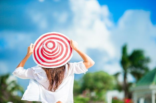 Belle jeune femme de détente sur le bord de la piscine infiniti, vue arrière de la fille en bikini et grand chapeau rouge