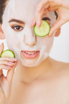 Belle jeune femme devient masque facial d'argile au spa, couché avec des concombres sur les yeux