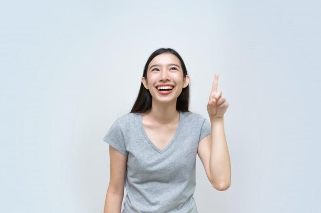 Belle jeune femme avec le doigt pointé vers le haut, portrait, jeune fille asiatique