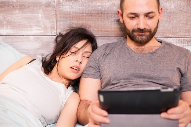 Belle jeune femme dormant à côté de son mari. l'homme utilise un ordinateur tablette.