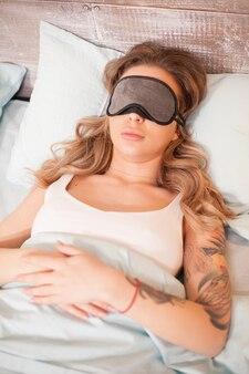 Belle jeune femme dormant avec un masque pour les yeux sur son oreiller.