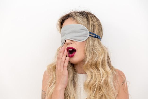 Belle jeune femme dort avec un masque pour les yeux.