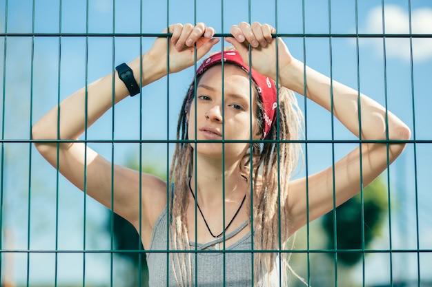 Belle jeune femme avec des dreadlocks vous regarde et ayant ses mains sur la clôture à mailles de chaîne