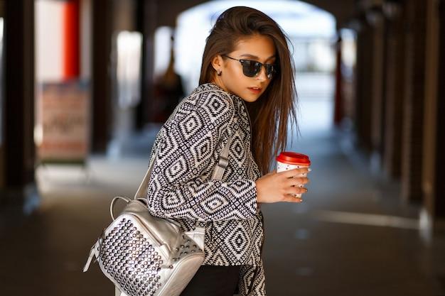 Belle jeune femme avec du café dans des vêtements à la mode avec un sac à dos marchant dans la ville