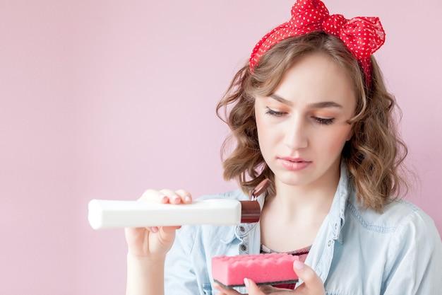 Belle jeune femme avec du maquillage et une coiffure avec des outils de nettoyage sur fond rose